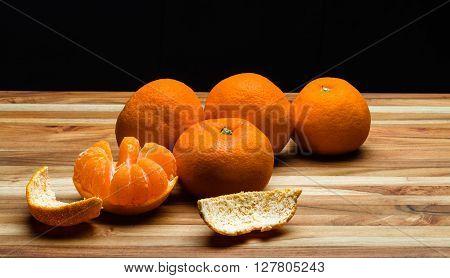 Peeled and unpeeled tangerines on a teak cutting board