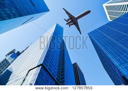 airplane over office buildings of new york