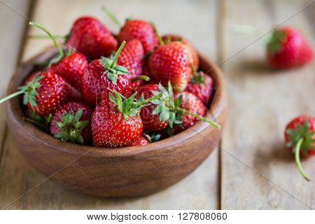 Fresh Strawberries in a wooden bowl on wooden board