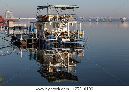 Pleasure boat and a river pier reflected on mirror water surface on clear summer morning. Embankment of the Dnieper River. Dnepropetrovsk. Ukraine