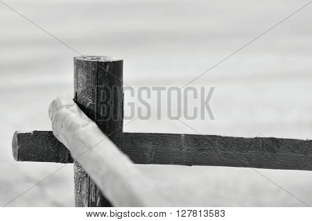 part of an old column and poles from a wooden fence for the ranch closeup on an indistinct background of monochrome tone