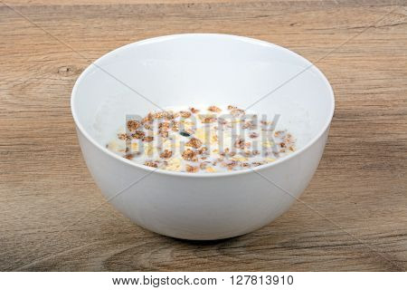 Muesli with a mix of healthy fruit nuts and seeds and milk in a dish against a wooden background.