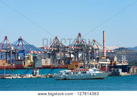 Container ships containers and cranes in the harbor of La Spezia Liguria Italy. In the background the Apuan Alps