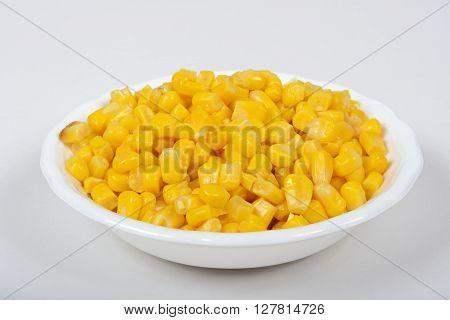Fresh sweet corn kernels in a white dish against a plain background.