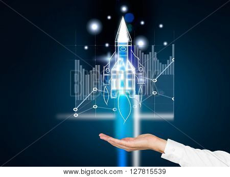 Startup concept with businessman hand holding digital rocket ship with business chart on dark blue background