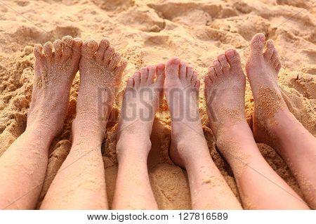 bare feet on the sandy beach close up photo
