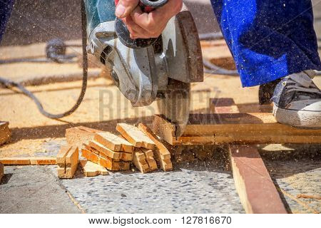 Carpenter using an electric saw cutting small wooden figures ** Note: Shallow depth of field