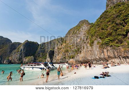 KO PHI PHI LEH, THAILAND - MARCH 2, 2016: Tropical island with crowd of tourists relaxing on sand of beautiful Maya Bay on March 2, 2015. Tropical Ko Phi Phi National Park covers about 39000 hectares