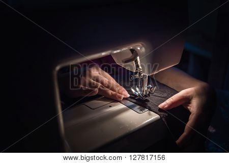 Close up of sewing machine on the table in the night.