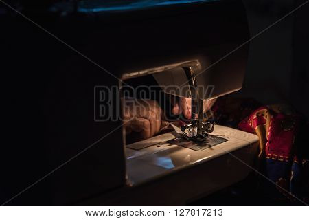 Close up of sewing machine on the table in the night. ** Note: Visible grain at 100%, best at smaller sizes