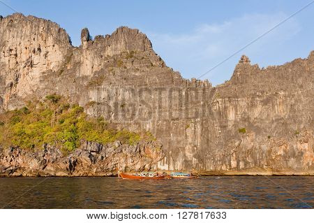 Popular diving point in Andaman Sea. Rocky cliffs and a fishers boat under blue sky. Beautiful landscape of fantastic Thailand