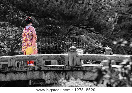 Black and white of a bridge in Kyoto with selective color on a young Geisha woman