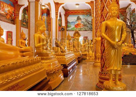 PHUKET, THAILAND - FEB 6, 2016: Crowd of golden Buddha statues in different poses inside Wat Chalong temple on February 6, 2016. First written mention about the buddhist monastery belongs to 1837