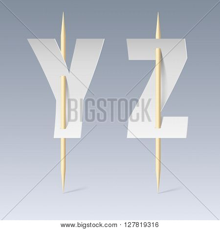 White paper cut font on toothpicks on grey background. Y and Z letters