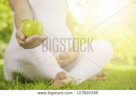 Pregnant woman relaxing in nature on a beautiful sunny day.Pregnant woman with fresh green apple.Pregnancy healthcare food and happiness concept.Healthy pregnancy.