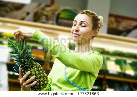 Woman doing shopping of merchandise in mega market.Beautiful mid adult woman shopping for fruits in a supermarket. Horizontal shot.