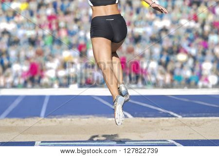 Female long jumpers jump into the sand box. In the background there can be seen fully occupied ranks with spectators.