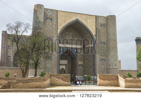 Samarkand, Uzbekistan - May 2, 2015: The large complex of Bibi-Khanym Mosque with the beautiful bright blue domes rich mosaic decorations and old hieroglyphs on its walls Samarkand Uzbekistan.