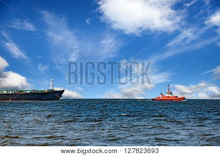 Cargo ship with escorting tug leaving port.