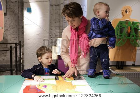 Mother with her two sons playing with puzzle in a museum