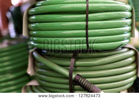 Green garden hoses coiled up and stacked on one another with shallow depth of field