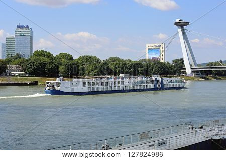BRATISLAVA SLOVAKIA - JULY 10: Cruise Ship at Danube River Bridge in Bratislava on JULY 10 2015. River Cruise Ship Pass Under Famous UFO Bridge in Bratislava Slovakia.