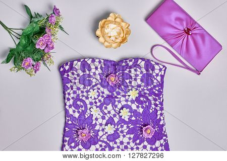 Summer Fashion Ladies, clothes accessories set. Glamor creative  purple dress, stylish handbag clutch, flowers, necklace. Overhead outfit. Top view, gray background