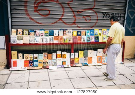 THESSALONIKI, GREECE - MAY 27, 2015: A man chooses a book in a bookshop. Books exhibited in the street.