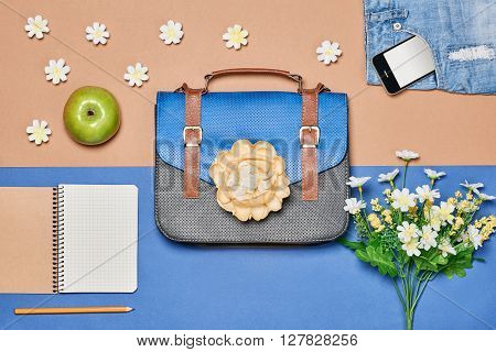 Overhead outfit Fashion woman set, accessories. Creative hipster look, pastel colors. Business handbag, denim shorts, smartphone, apple and flowers.Unusual urban essentials. Top view, blue background
