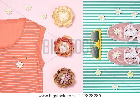 Overhead outfit Fashion girl clothes set, accessories. Creative hipster look, pastel colors. Stylish gumshoes, t-shirt, sunglasses, flowers. Unusual modern summer essentials.Top view, green background