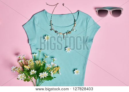 Overhead outfit Fashion Ladies, clothes accessories set. accessories. Creative T-shirt, flowers, necklace, sunglasses, bouquet of camomile. Unusual modern elegant essentials.Top view, pink background