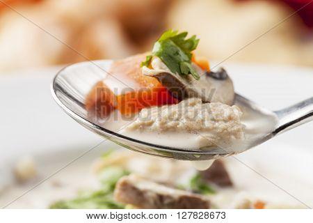 thai tom kha gai soup on a spoon