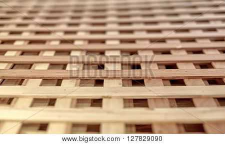Close Up Wood lattice for growing vines and other plants in a garden with shallow depth of field