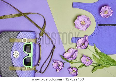 Overhead outfit Fashion woman set, accessories. Creative hipster look, pastel colors. Stylish handbag, dress, sunglasses and flowers. Unusual urban essentials. Top view, purple green background