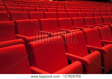 Empty theater with abstract red seats and black carpet