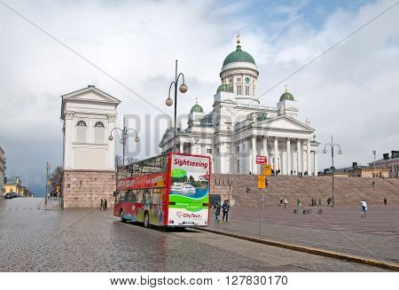 HELSINKI, FINLAND - APRIL 23, 2016: Hop-On Hop-Off. City Tour Bus on The Senate Square near Helsinki Cathedral. Traveling In the bus can see the best sights and listen to the excursion in ten languages