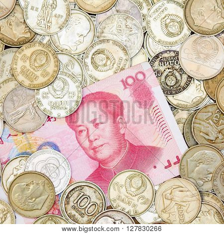 Photo of one hundred yuans lying on heap of old coins. Currency exchange illustration