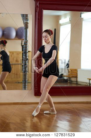 Beautiful young female classical ballet dancer on pointe shoes wearing a black leotard and shorts in class classical dance against mirror. Ballet