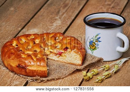 Piece of apple pie on sackcloth, metal mug and green plant sprig on planked wooden table
