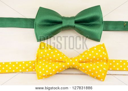 Green and yellow bow ties on a wooden table