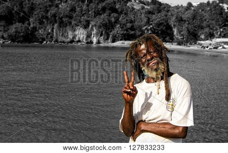 Castries St. Lucia - November 26 2015: homeless dark skinned man with messy hair showing tongue at fishing village suuny day outdoor