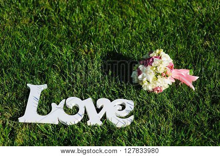 Sign of Love and wedding bouquet on a green lawn.  Wedding concept. Word Love of the wooden letters on a green grass, wedding decor, wooden letters Love.