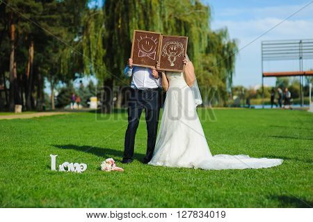 Bride and groom hold chalkboard with funny faces. Bride and groom holding blackboard in front of their faces. Man and woman cover their faces blackboard. Sign of Love, wedding bouquet on green lawn.
