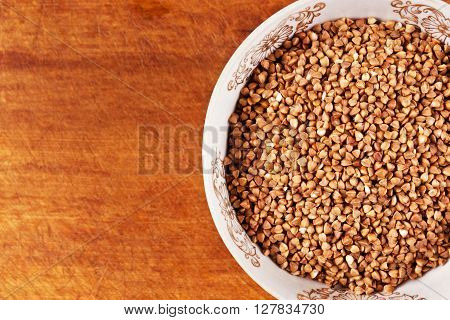 Buckwheat groats in a bowl on a wooden background