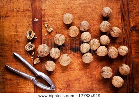 Walnuts with nutcracker on rustic wooden background, selective focus