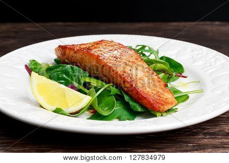Fried salmon fillet served with vegetables and lemon.