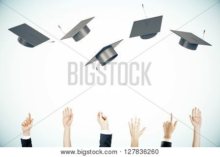 Graduation concept with businesspeople hands throwing up graduation caps on light background