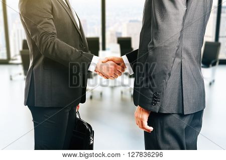 Businesspeople shaking hands on office background, close up