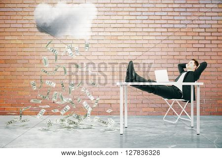 Financial growth concept with businessman sitting at table with feet up and looking at abstract money rain in red brick interior. 3D Rendering