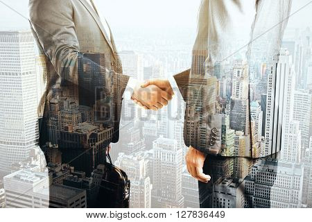 Businesspeople shaking hands on cityscape background. Double exposure